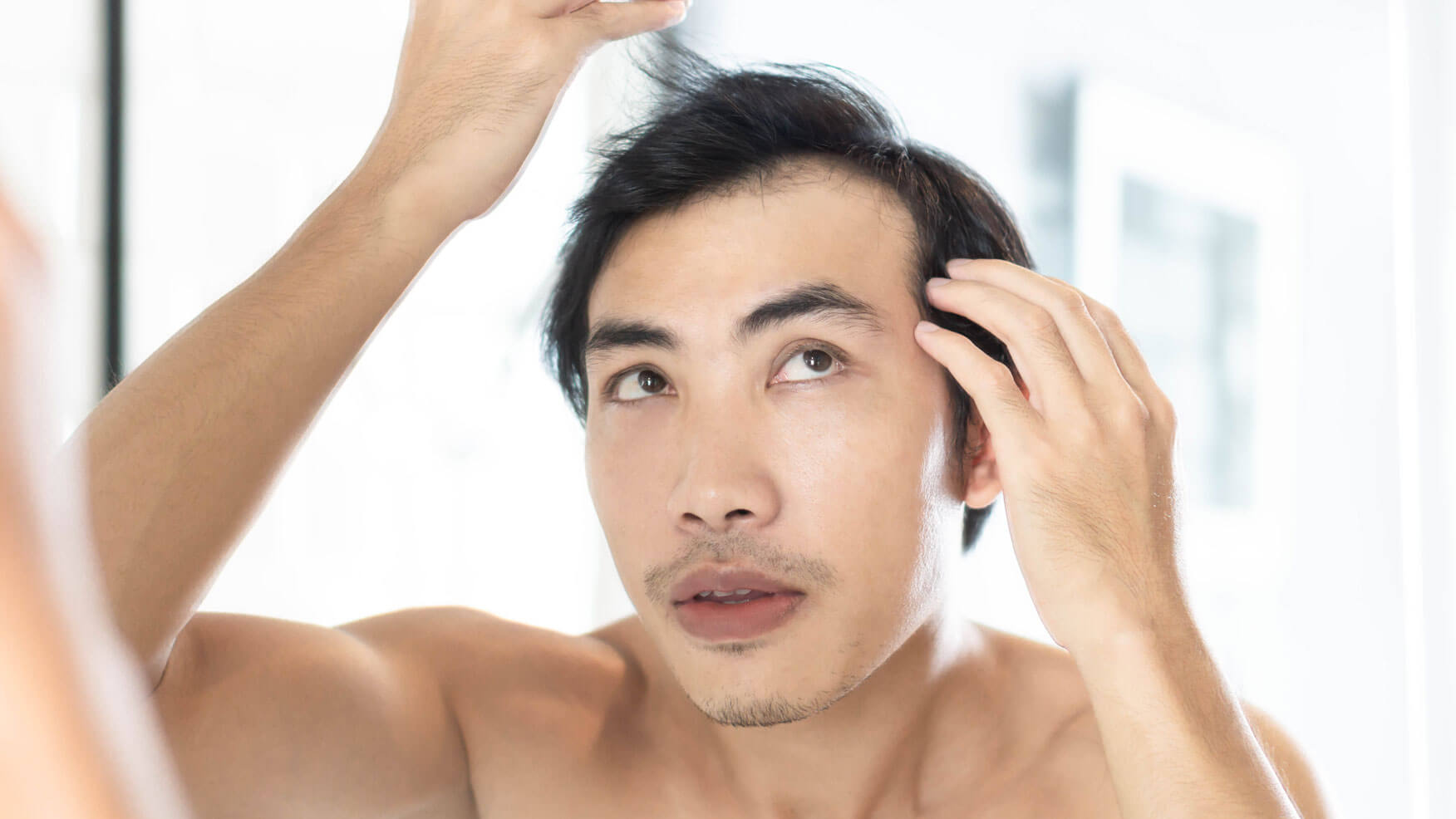 A topless man examining his hair in the mirror