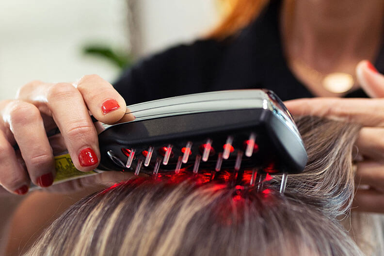 A woman using a LLLT hairbrush on a person's hair