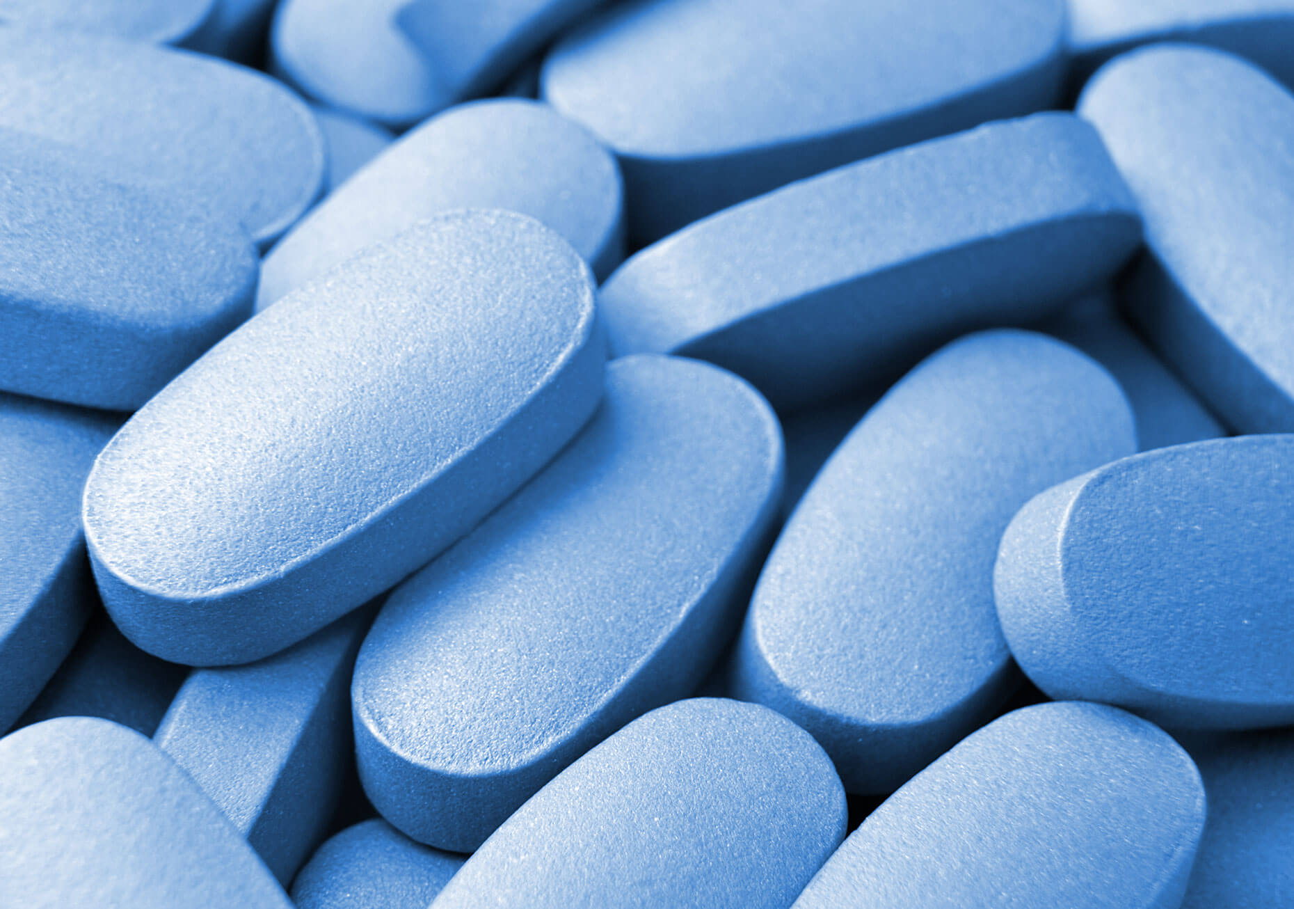 A close-up of various blue, oval pills