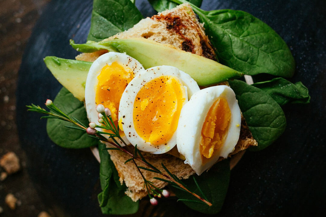 Halved, boiled eggs and avocado slices on toast rest on a bed of fresh spinach