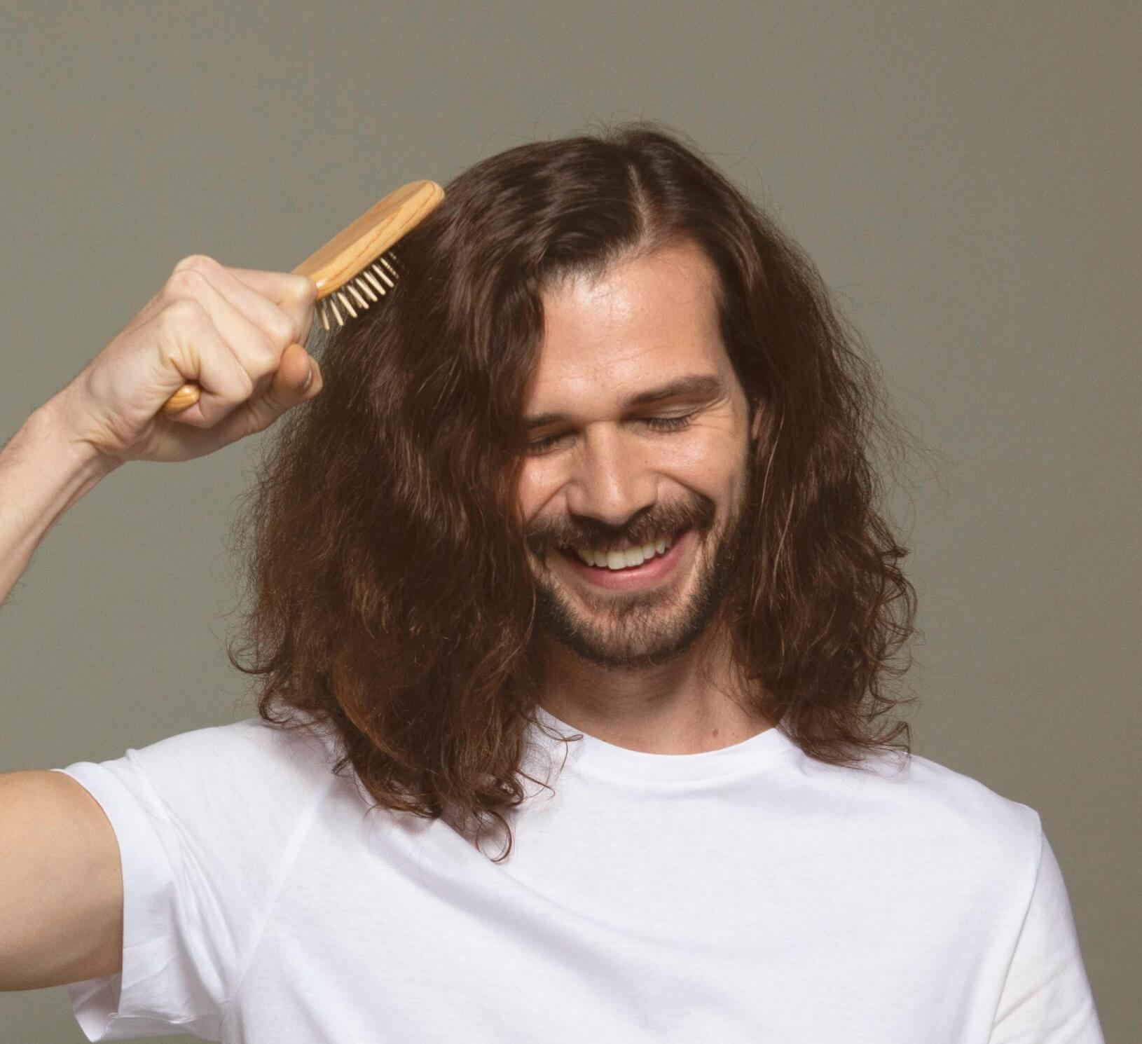 A man in a white t-shirt brushing his shoulder-length, wavy hair