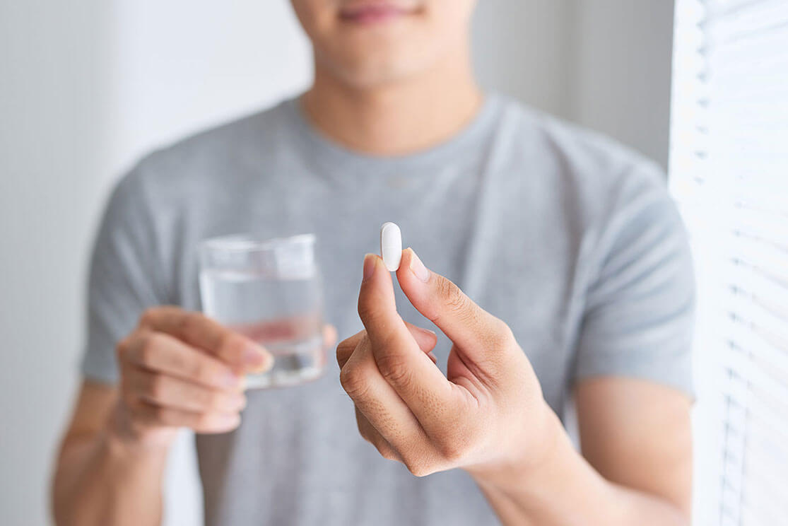 Close-up of the torso of a man holding  a supplement and water in his hands