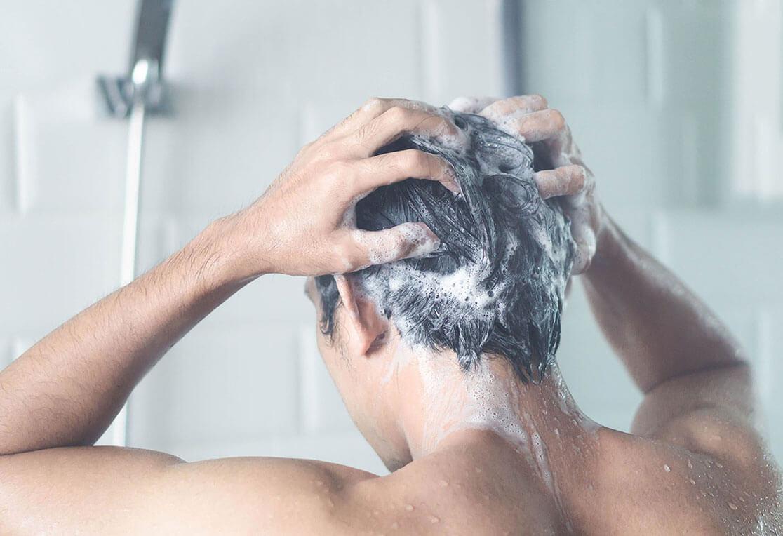 A man facing backwards, shampooing his hair in the shower
