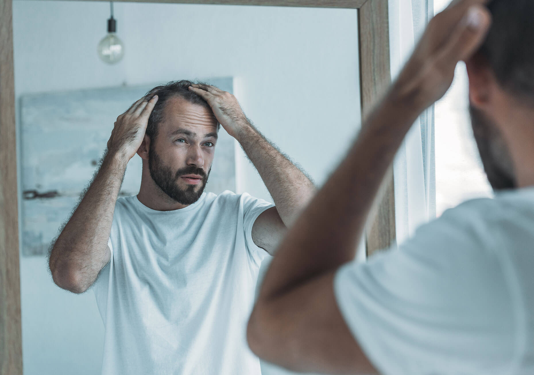 A man inspecting his hairline in the mirror