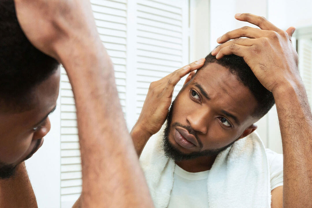 A man inspects his hair and side of his head in a mirror
