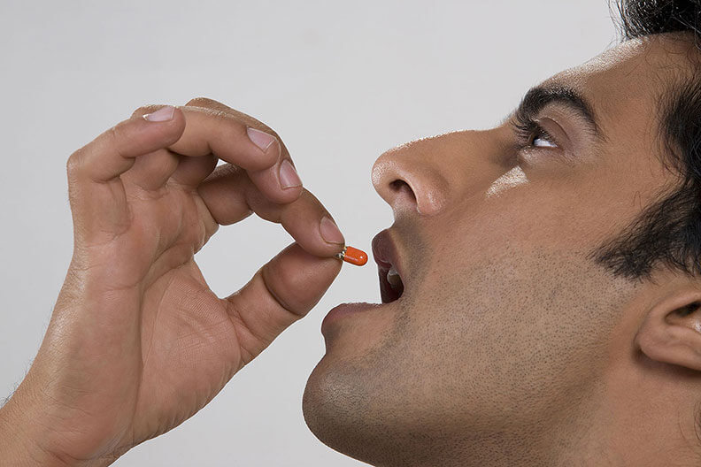 A close up of a man holding an orange capsule to his mouth