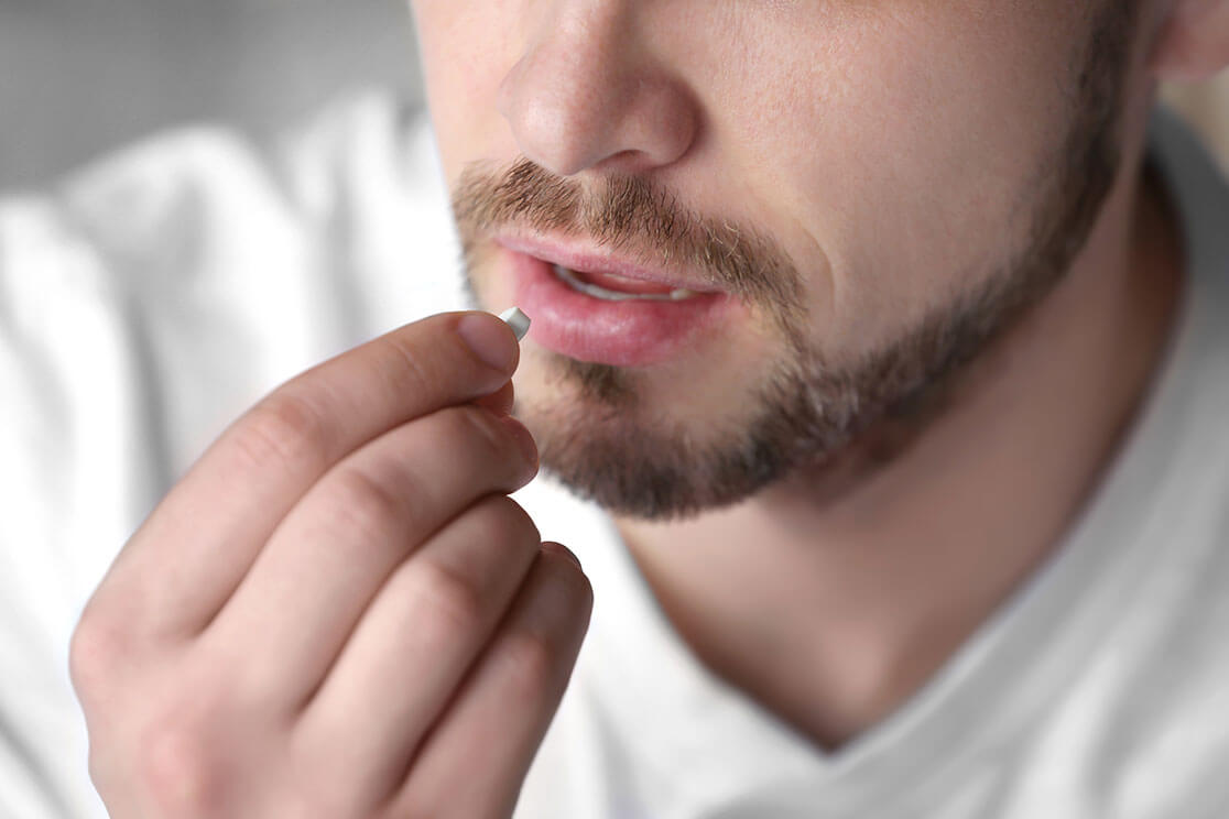 Close-up of a man holding a pill to his mouth