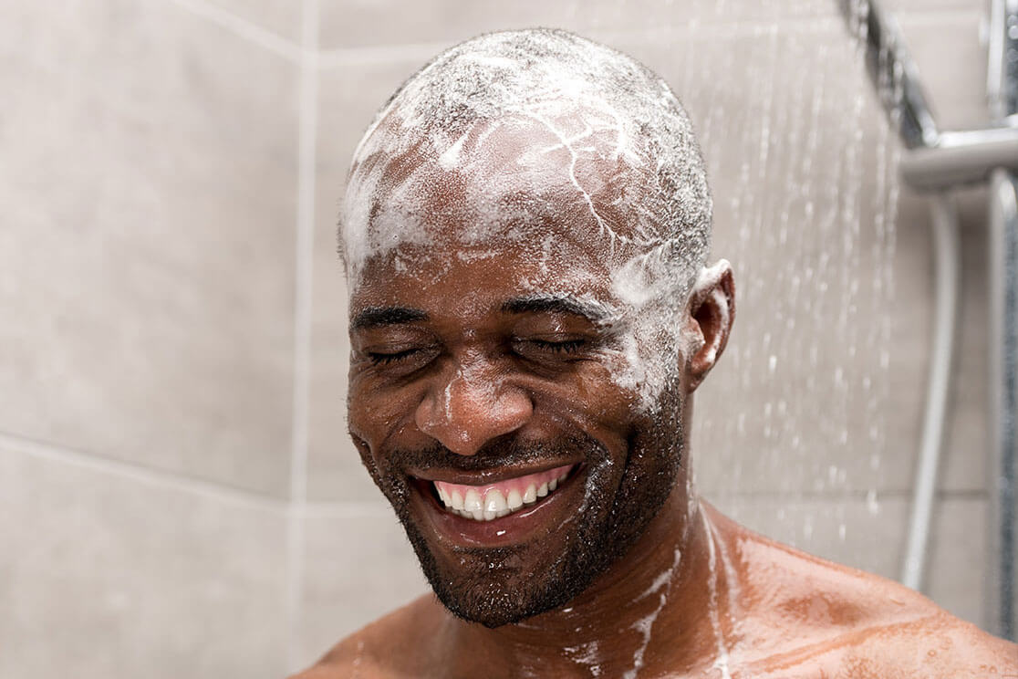 A man in the shower with shampoo on his head