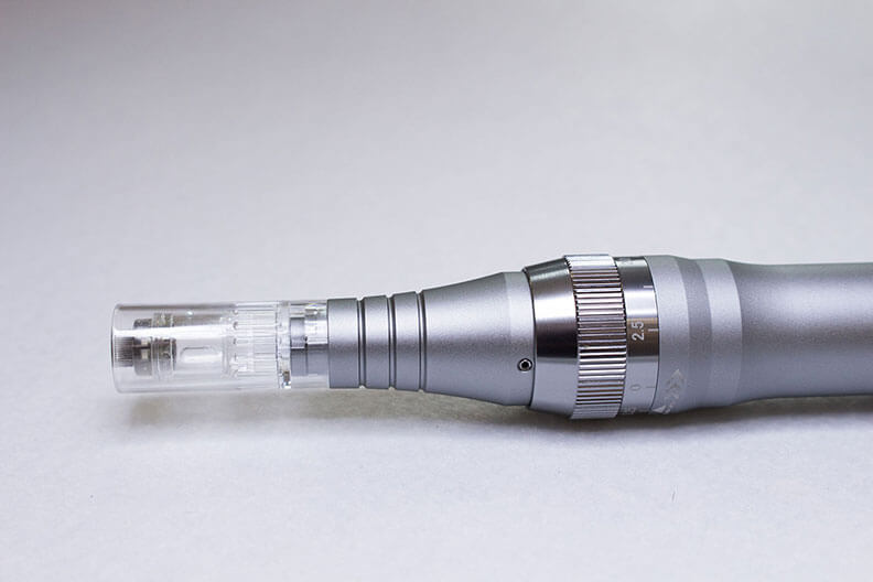 The tip of a silver microneedling device