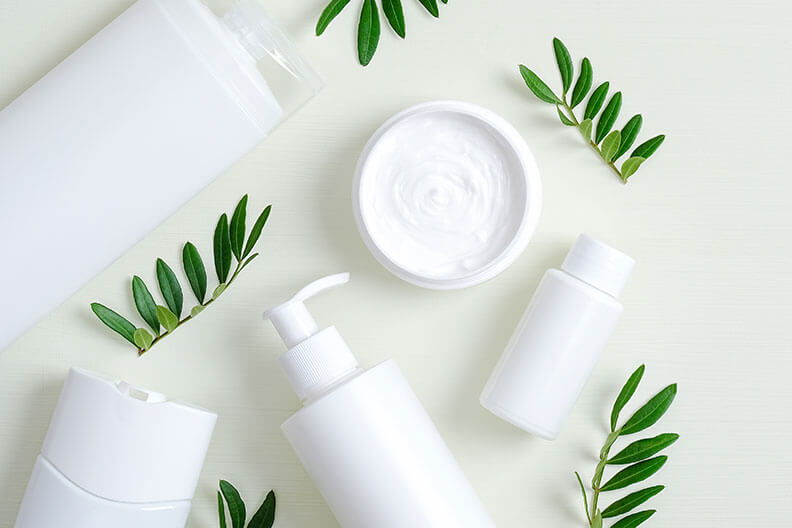 White containers of different shapes and sizes alongside ferns