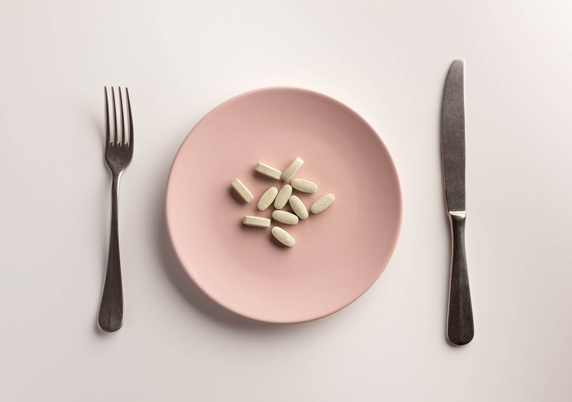 Supplements on a pink plate, with a fork and knife on either side