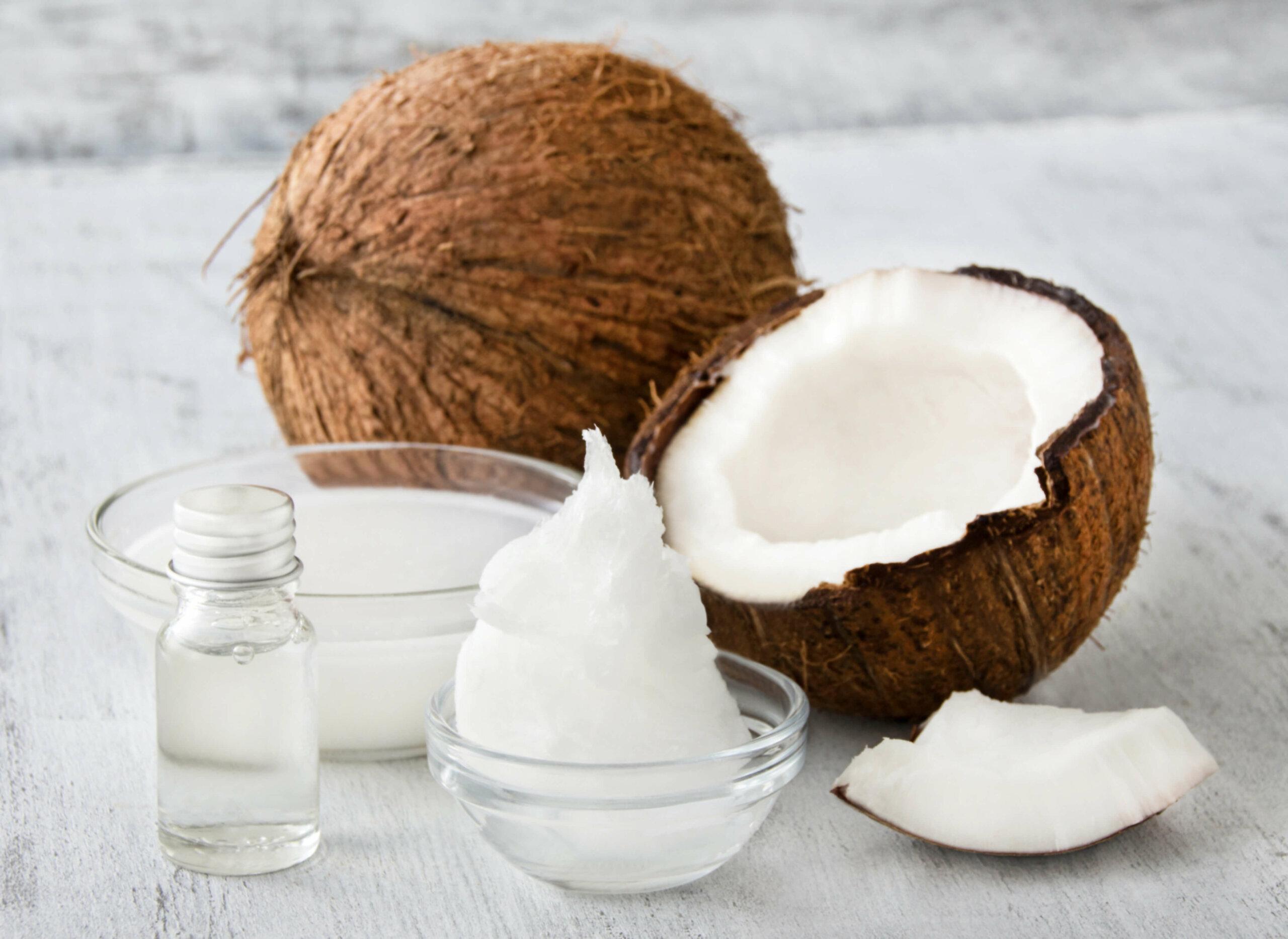 A coconut and halved coconut alongside coconut oil and coconut butter