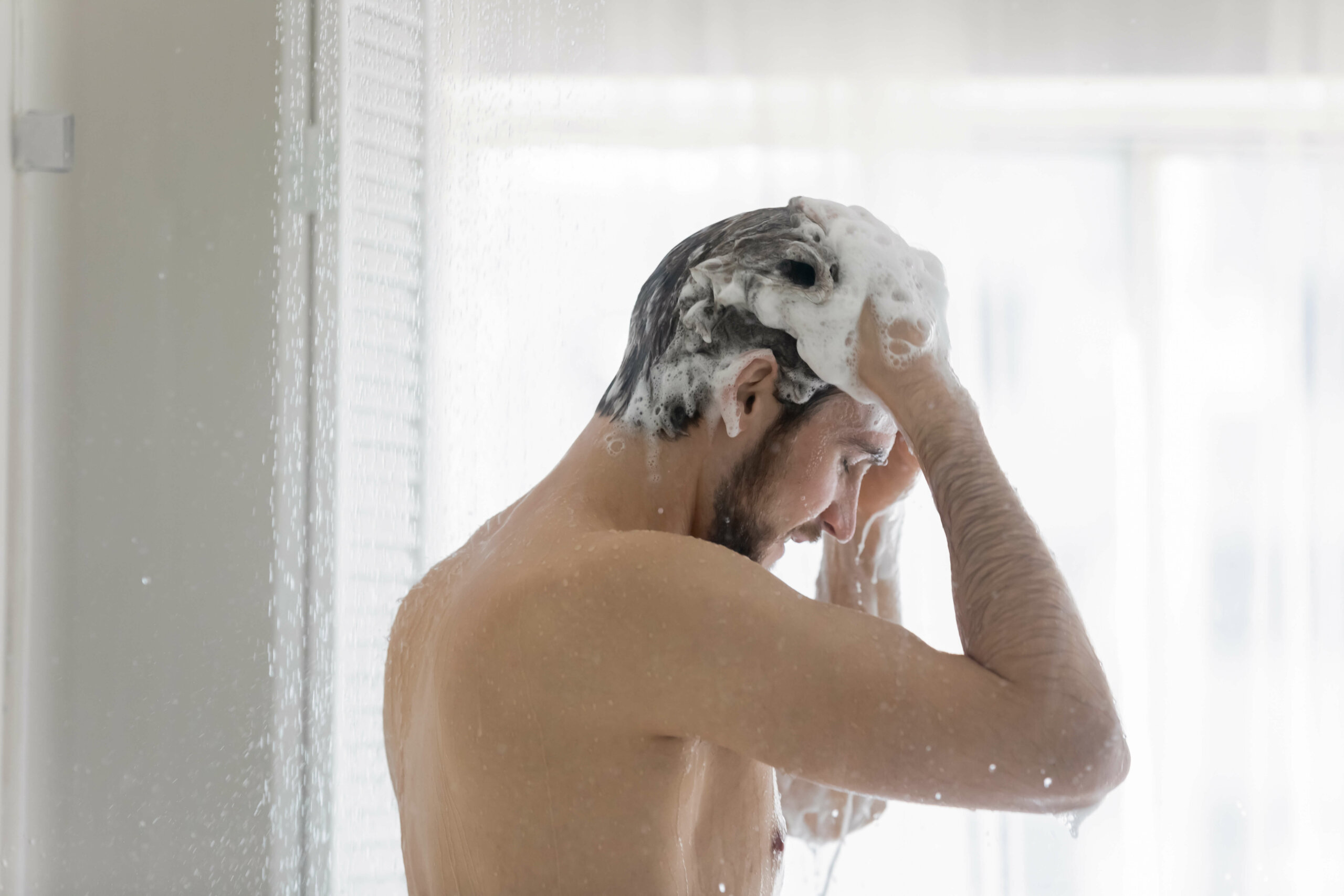 A man standing in the shower, washing his hair with minoxidil shampoo