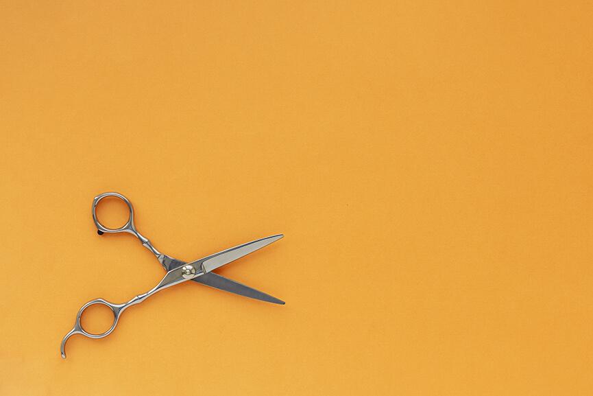 Hairdressing scissors against an orange background