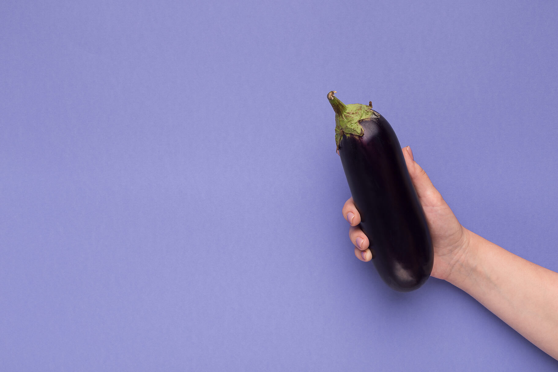 Man's hand holding up an eggplant against a purple background