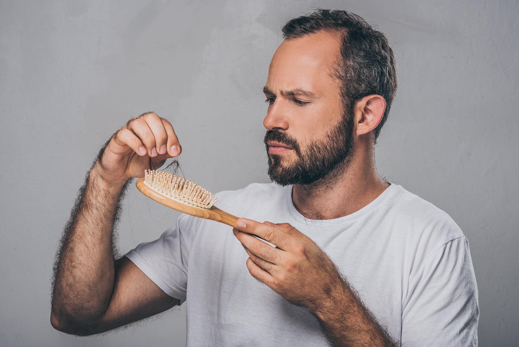 man inspecting hair left on a hairbrush