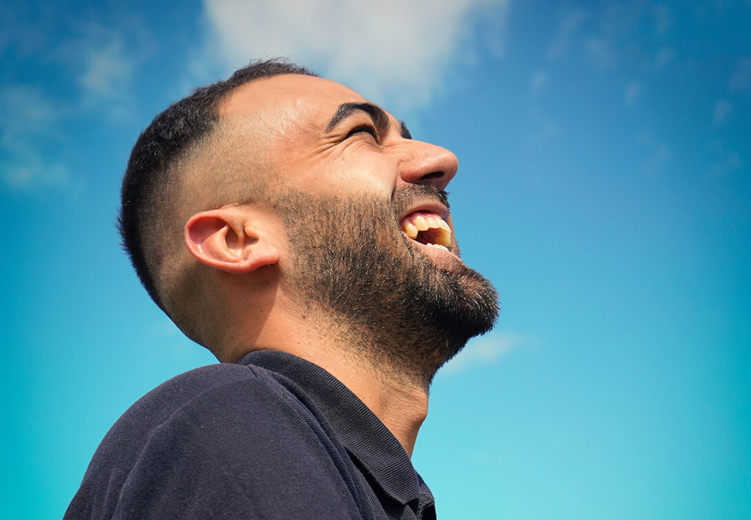 close-up of a laughing man with a long buzz cut