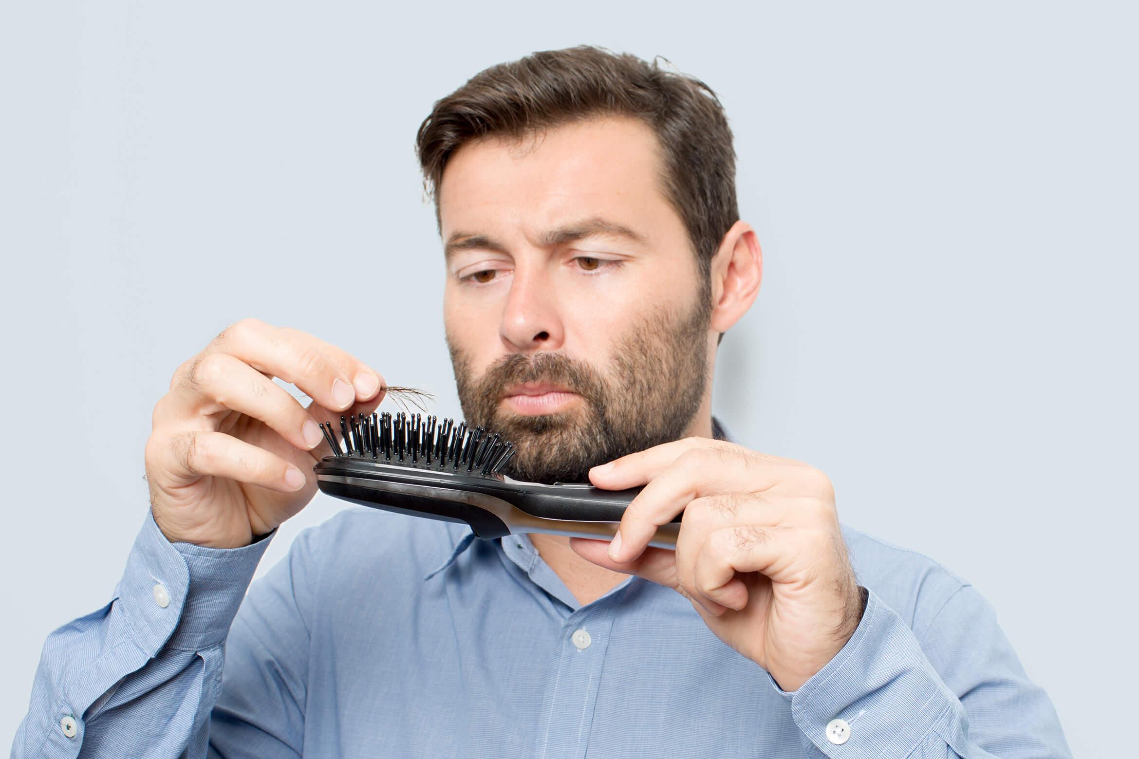 A man inspecting hair left on a hair brush