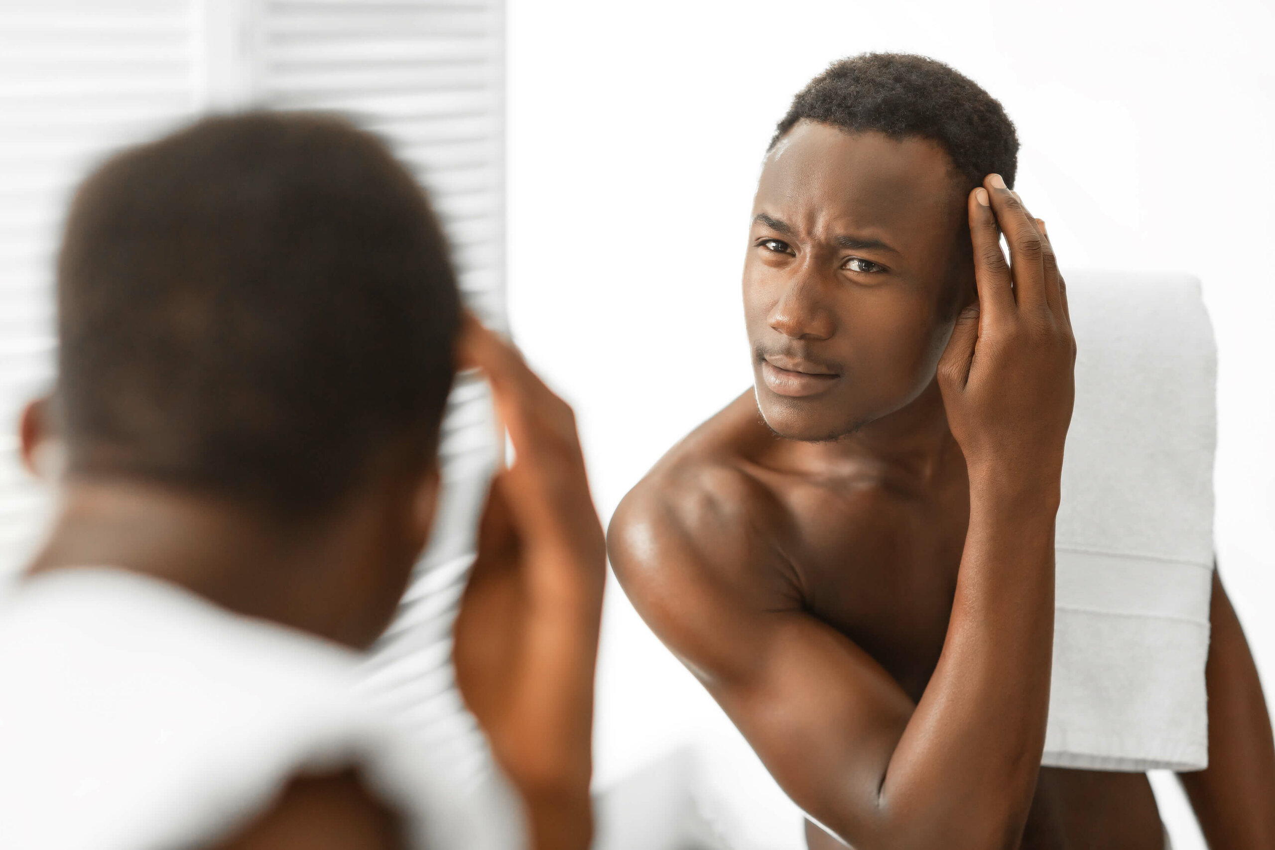 A shirtless African American man inspecting his hairline in the bathroom mirror