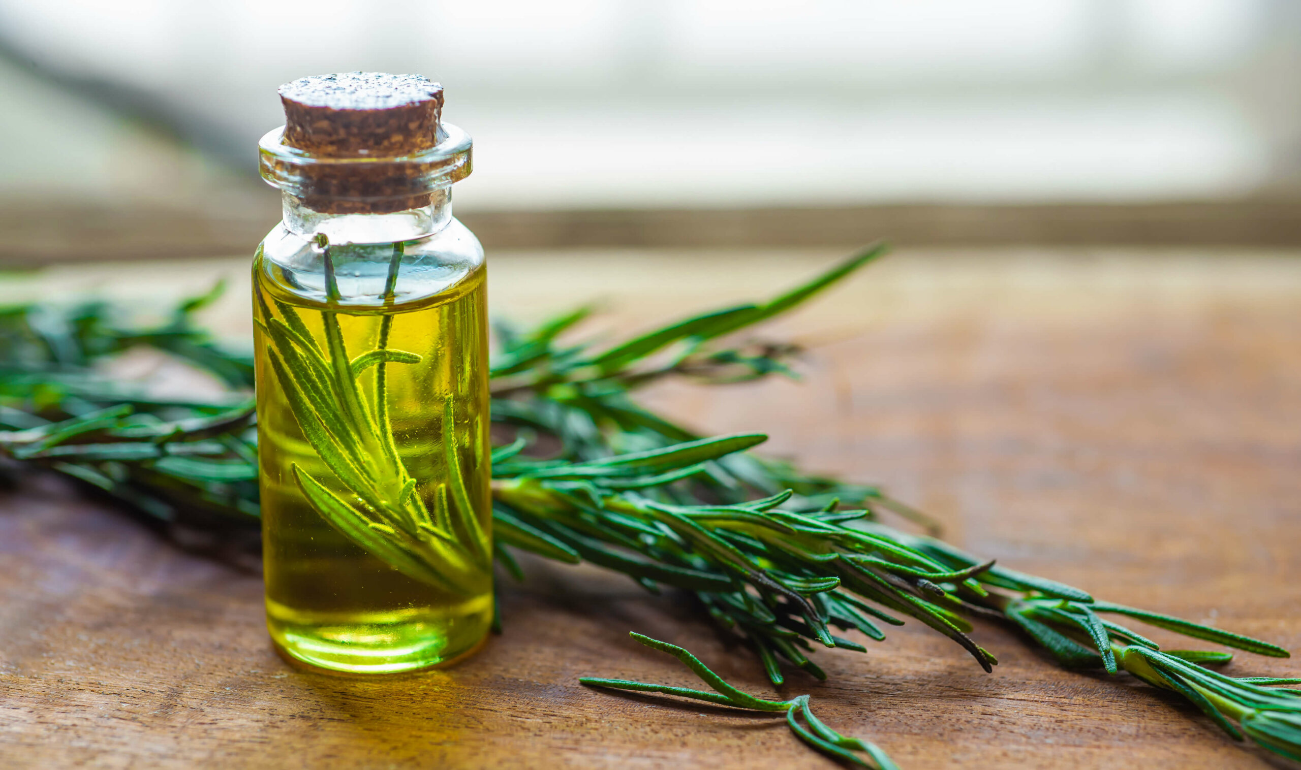 Sprigs of rosemary next to a small container of rosemary-infused oil