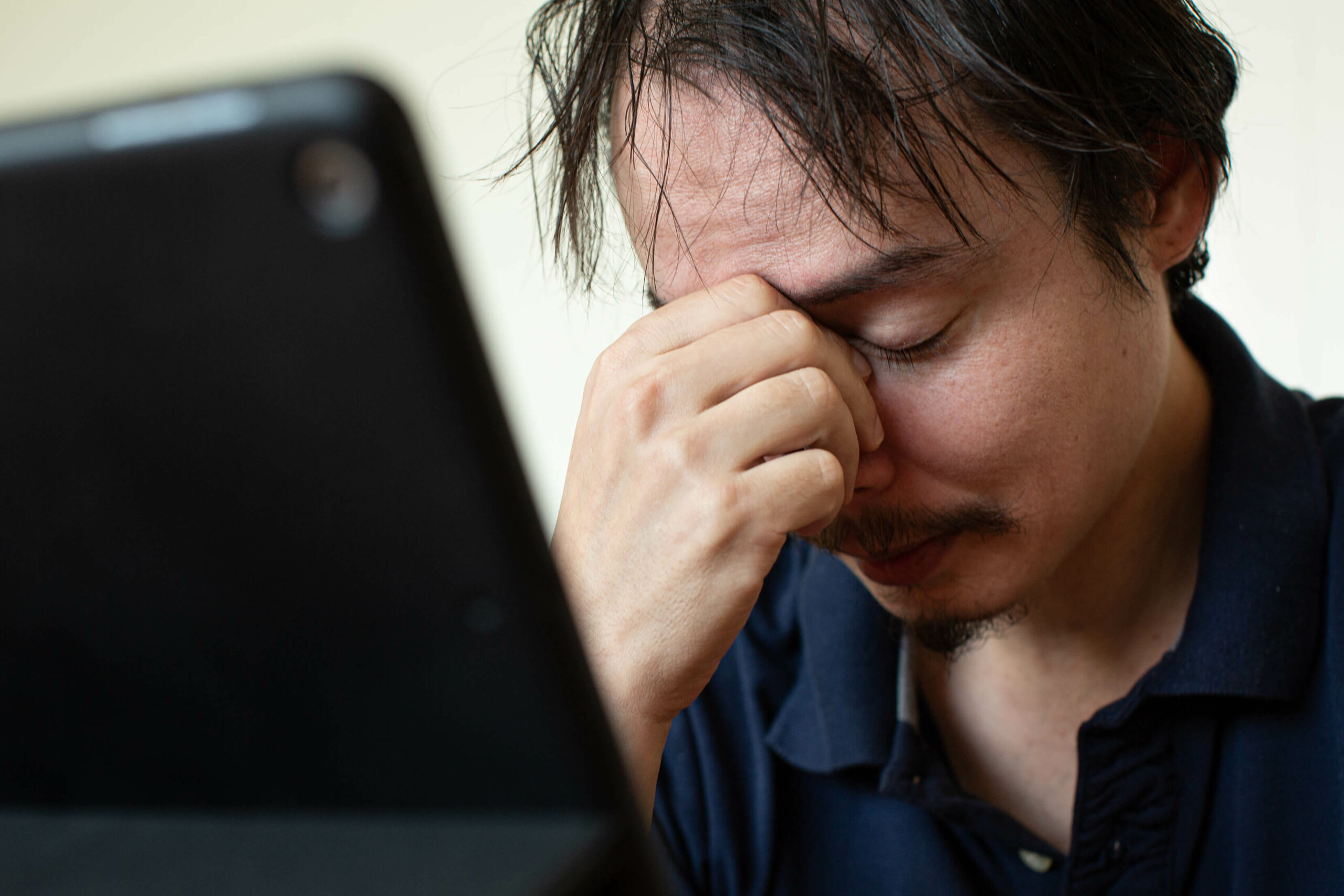 An electronic device next to a man, who is holding the bridge of his nose with one hand and looking stressed out.
