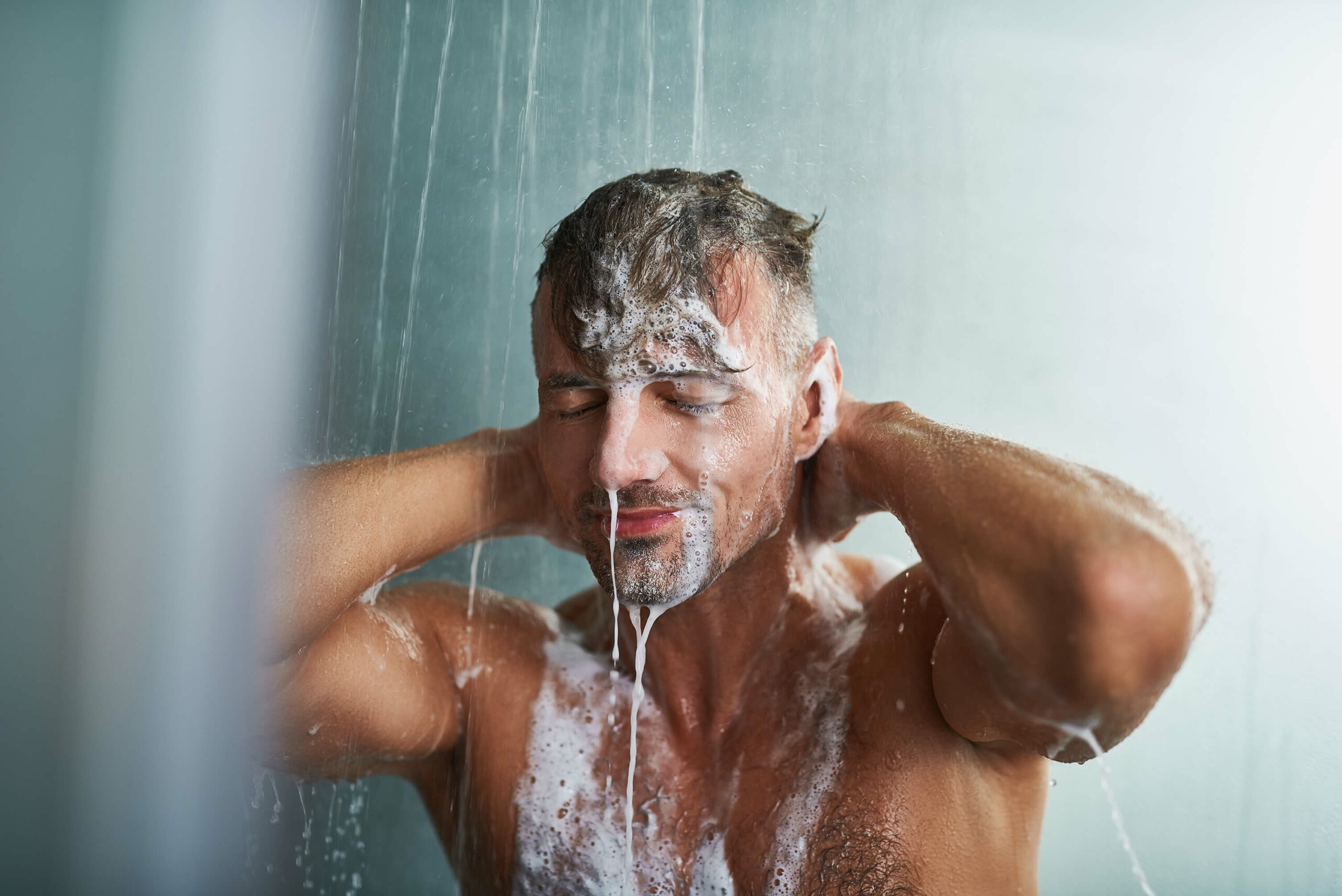 The upper body of a man covered in soap suds washing himself off in the shower