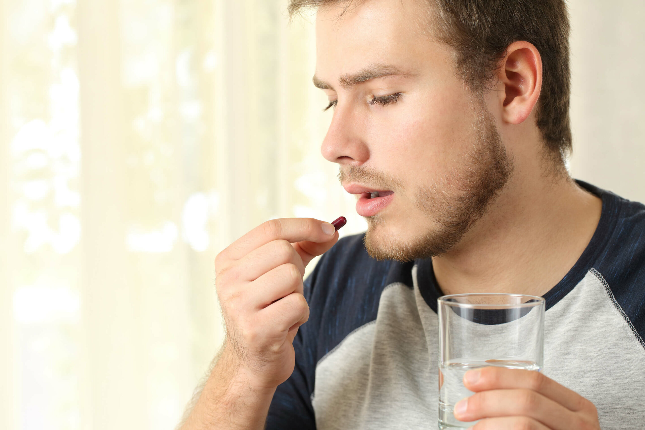 A close-up of a man holding a pill to his mouth