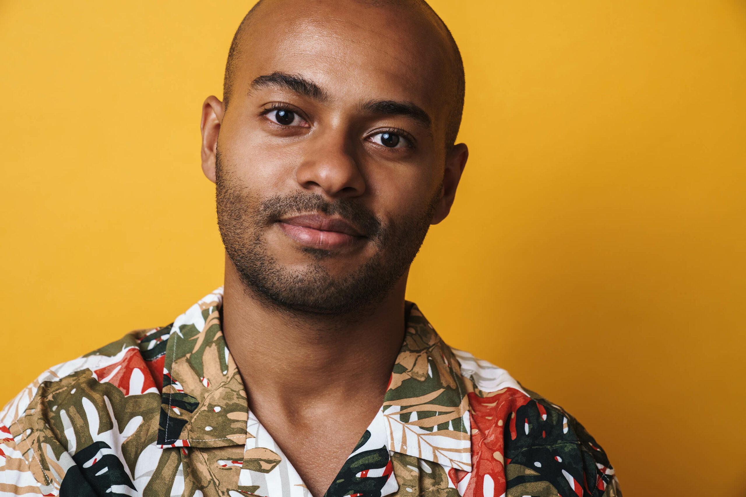 A close up of a man with a shaved head and bright floral shirt
