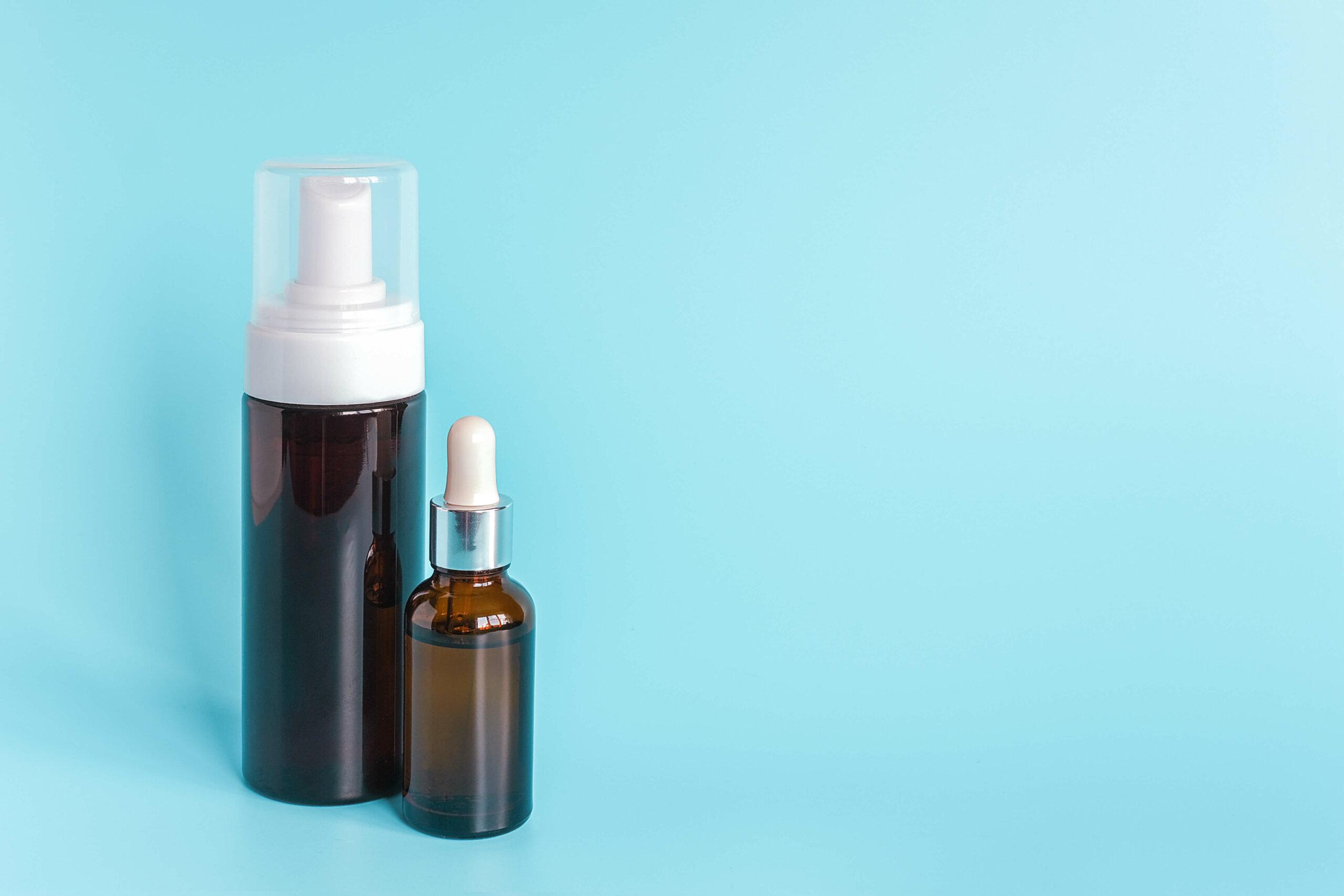 A dark bottle of foam next to a dark bottle of serum, against a blue background