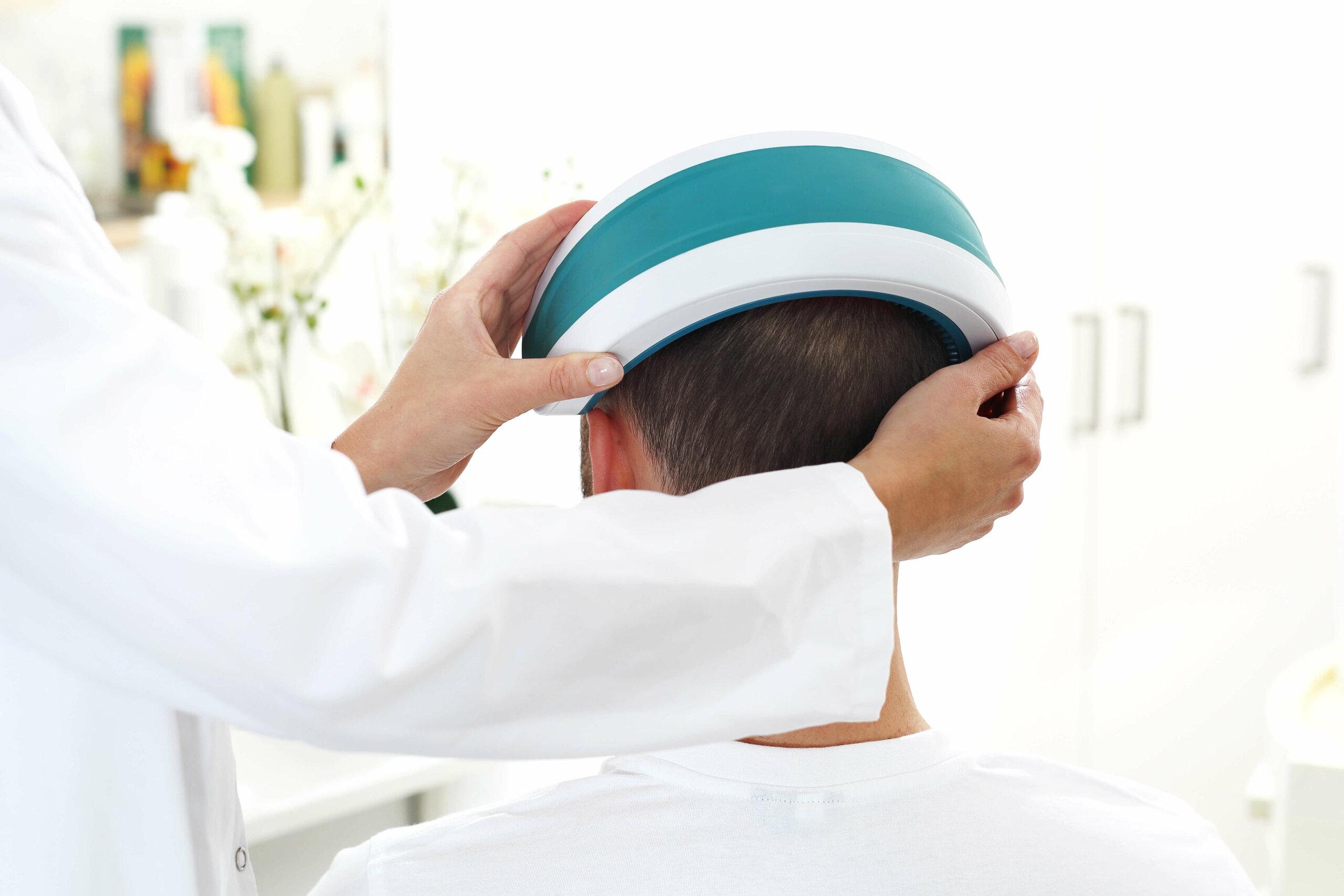 A medical professional applying an LLLT headband to a man's head