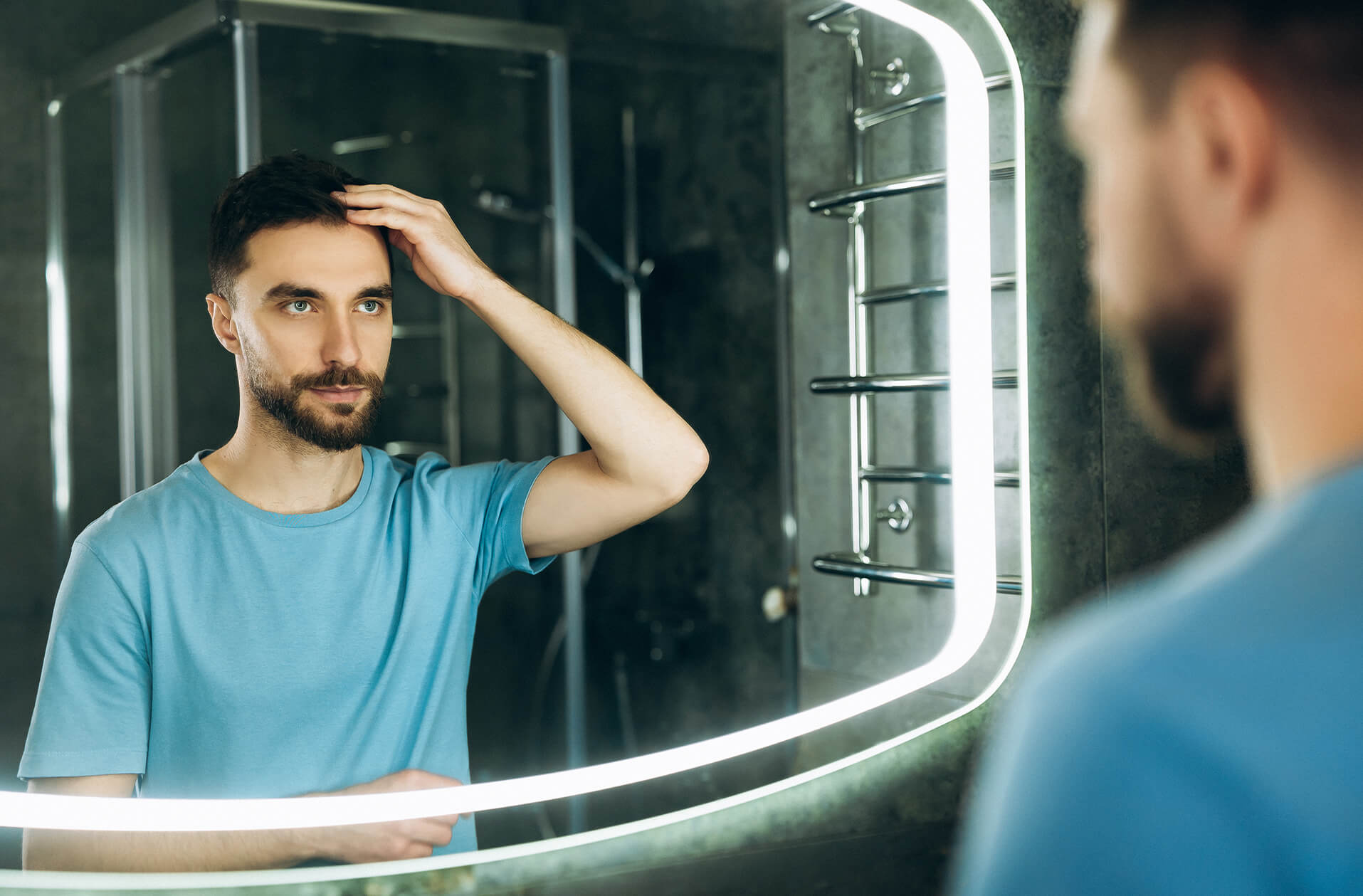 A man inspecting his hairline in a bathroom mirror
