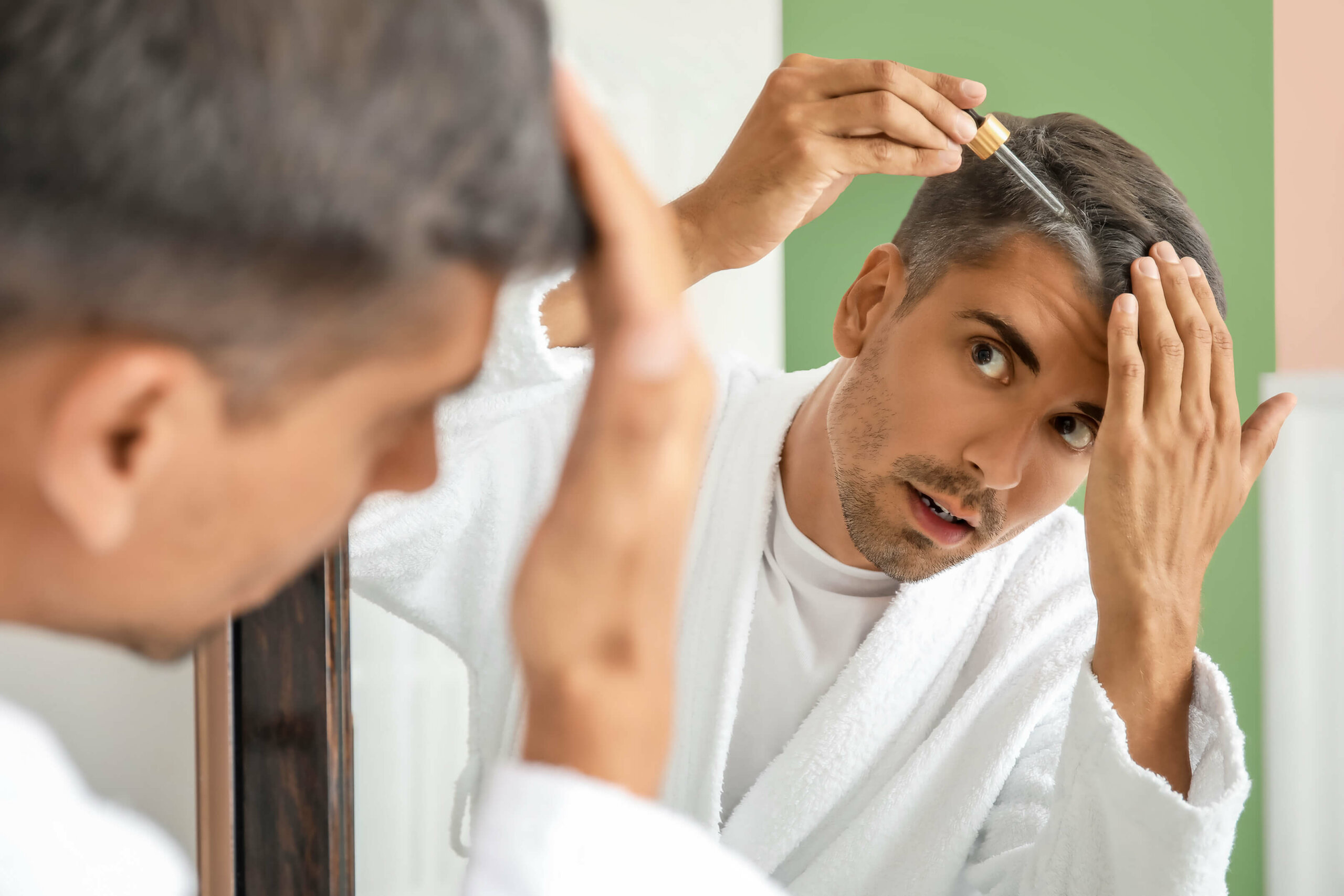 A man in a bathrobe applying liquid minoxidil to his scalp with a dropper