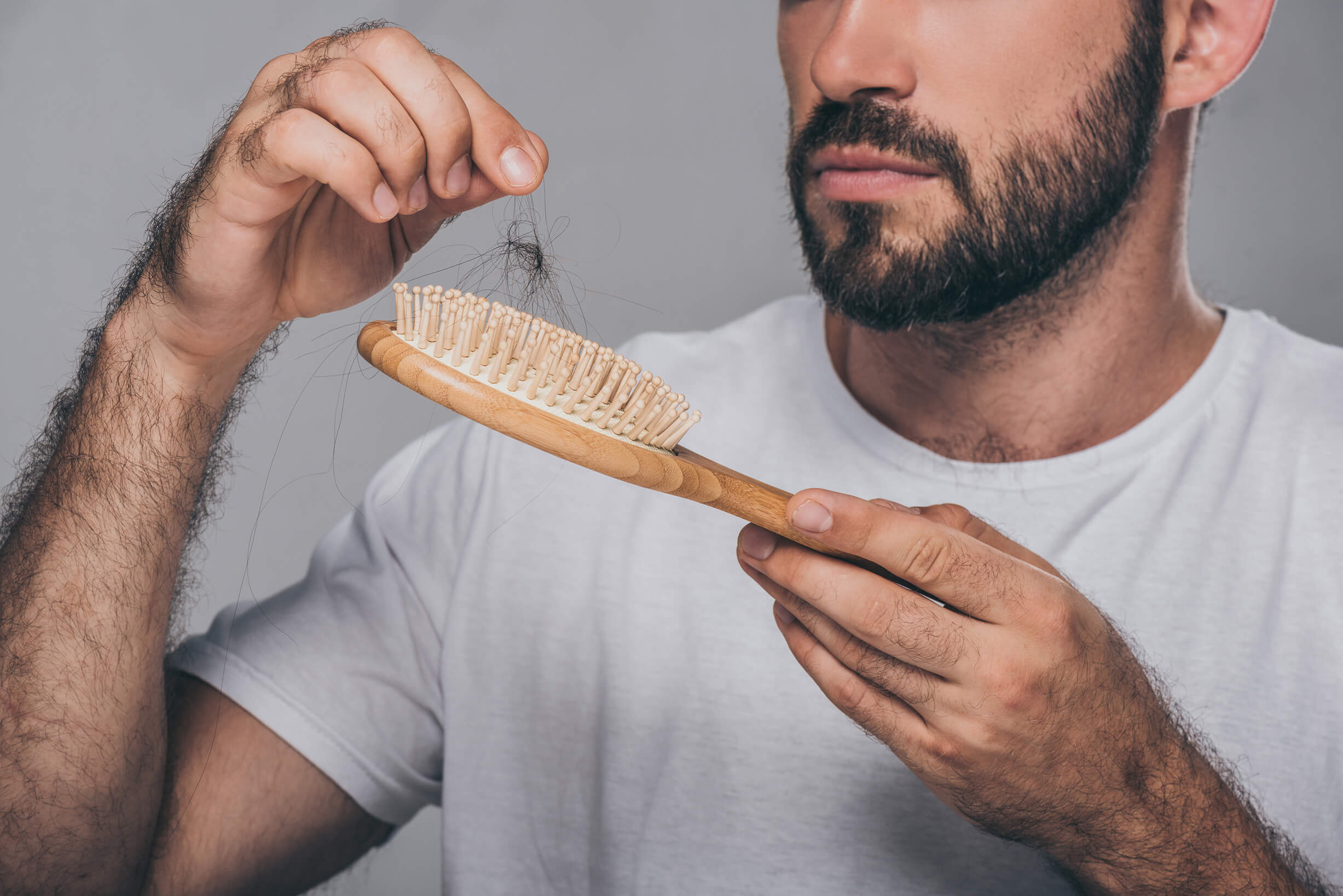 A close-up of a man picking out hairs from a hair brush