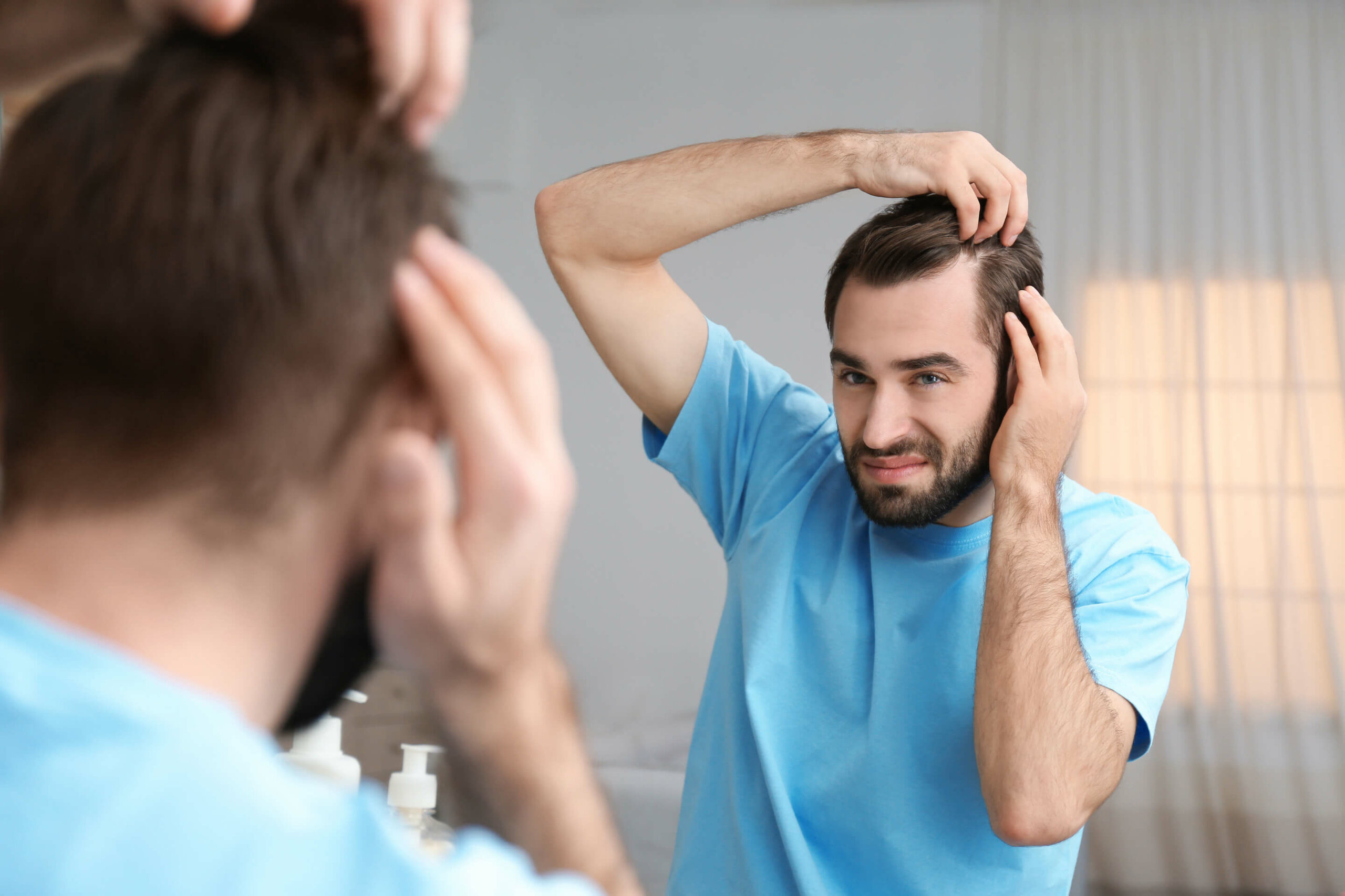 A man in a t-shirt inspecting his temples in the mirror, looking for signs of hair loss