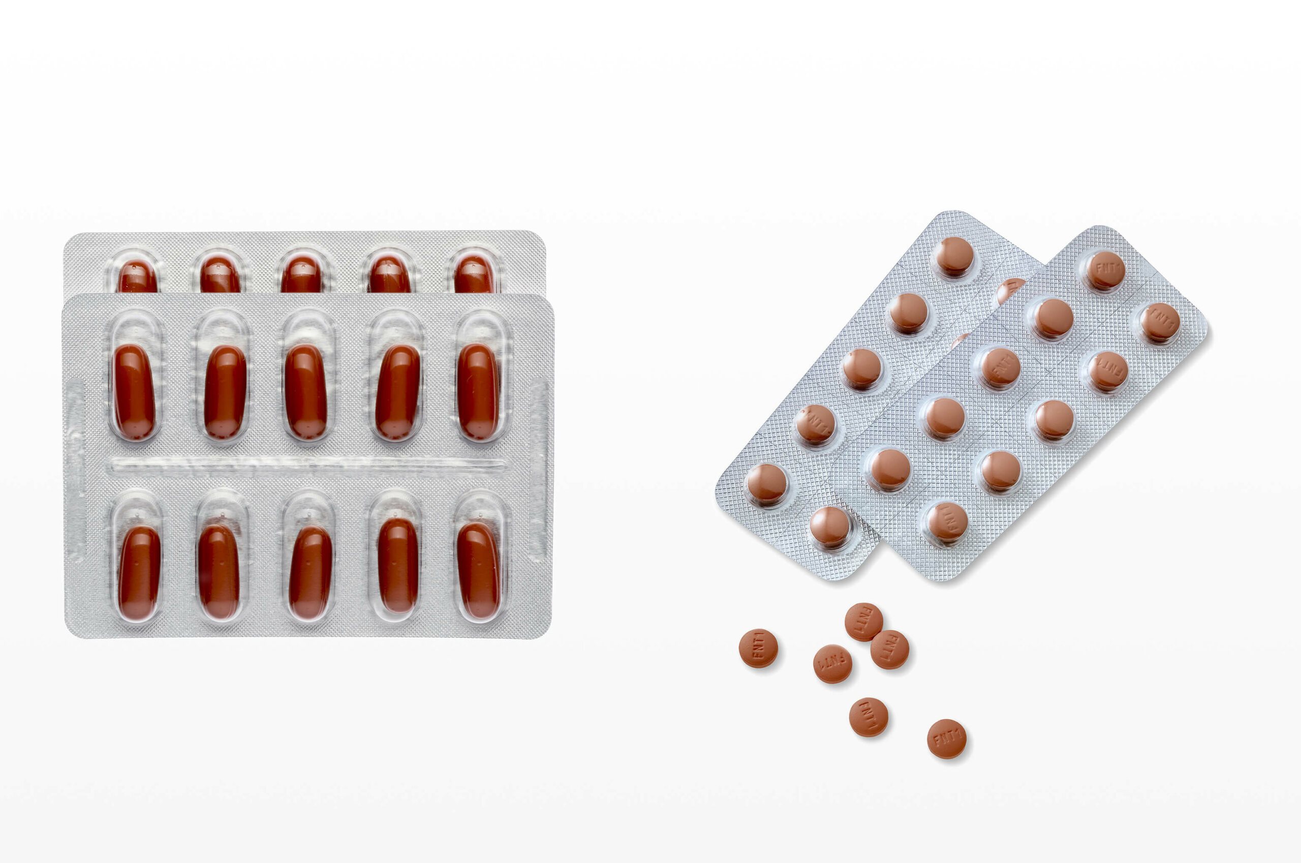 A double packet of oval, red dutasteride pills on the left, next to a double packet of circular, red finasteride pills on the right
